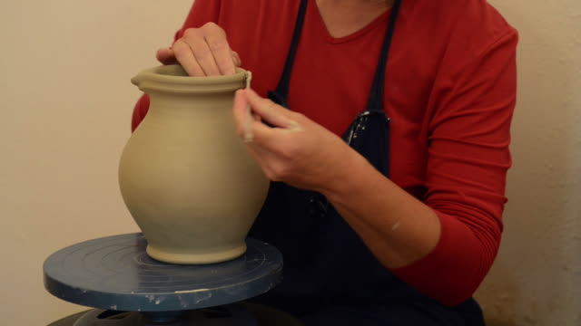 ms shot of female potter makes a handle to pitcher / landshut, bavaria, germany - pitcher jug stock videos & royalty-free footage