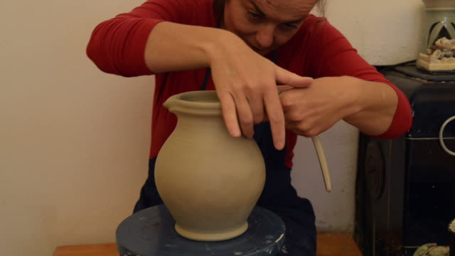 ms td shot of female potter makes handle to pitcher / landshut, bavaria, germany - pitcher jug stock videos & royalty-free footage