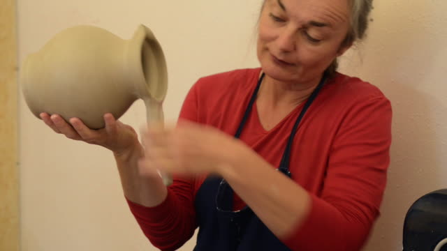 ms shot of female potter shapes and makes handle to pitcher / landshut, bavaria, germany - pitcher jug stock videos & royalty-free footage