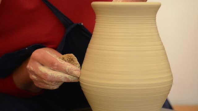 cu tu shot of female potter shapes pitcher on potterwheel at pottery / landshut, bavaria, germany - tonkeramik stock-videos und b-roll-filmmaterial