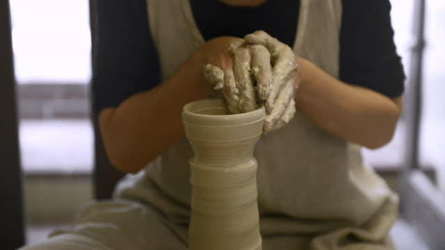 ms shot of female potter shaping  pot from lump of clay on potters wheel at pottery / kyoto, japan - pottery stock videos & royalty-free footage