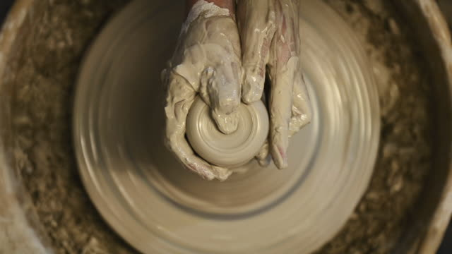 cu shot of female potter shaping  pot from lump of clay on potters wheel at pottery / kyoto, japan - 技能点の映像素材/bロール