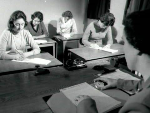 Shot of female students at the BBC secretarial school taking down shorthand while a female instructor times them with a stopwatch 1959