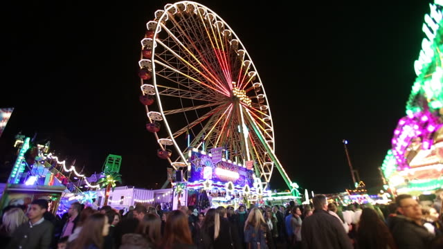 ws la shot of ferris wheel and people passing by at fun fair / cologne, germany - 遊園地点の映像素材/bロール