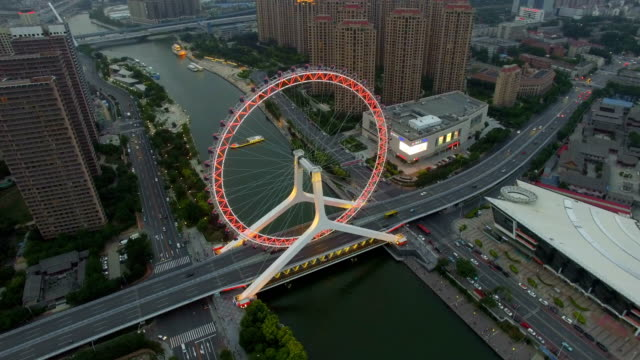T/L AERIAL shot of Ferris wheel over river and cityscape at night/Tianjin,China