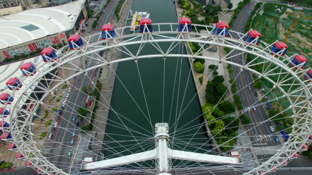 AERIAL shot of Ferris wheel over river and cityscape/Tianjin,China