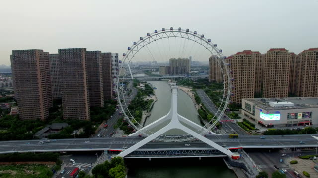 aerial shot of ferris wheel over river and cityscape/tianjin,china - big wheel stock videos & royalty-free footage