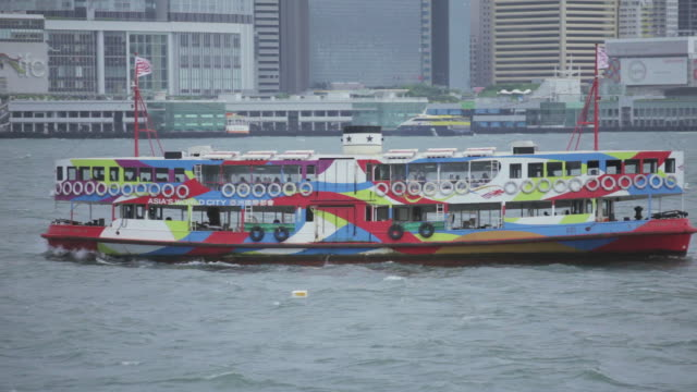 ms ts shot of ferry moving in bay channel between hong kong and kowloon / hong kong - traghetto star video stock e b–roll