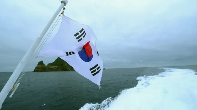 MS POV Shot of ferry to dokdo Island with South Korean flag (Natural Monument Heritage and one of most famous island in Korea) / Uleung, Gyeongsangbuk-do, South Korea