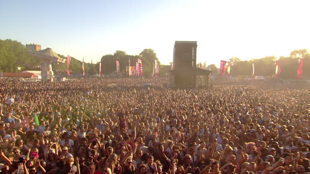 cu pov tu shot of festival crowd dancing at barrier crowd jumping around sunny sunglasses laughter and smiles with hands up in air / victoria park, london, united kingdom  - kraneinstellung stock-videos und b-roll-filmmaterial