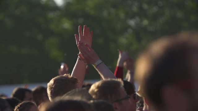 MS SLO MO Shot of Festival crowd hands in air clapping festival bands on wrists / Victoria Park, London, United Kingdom