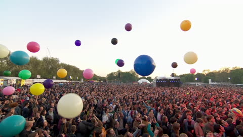 ms ts pov shot of festival crowd hitting multi-colour big balloons into sky / victoria park, london, united kingdom - konzert stock-videos und b-roll-filmmaterial