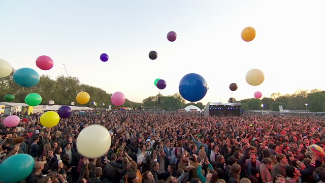ms ts pov shot of festival crowd hitting multi-colour big balloons into sky / victoria park, london, united kingdom - spettatore video stock e b–roll