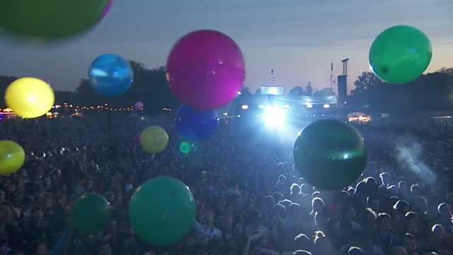 MS ZO POV Shot of Festival crowd hitting multi-colour big balloons into sky / Victoria Park, London, United Kingdom