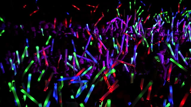 MS R/F Shot of Festival crowd with giant glow sticks at night. Extreme Close Up / Victoria Park, London, United Kingdom