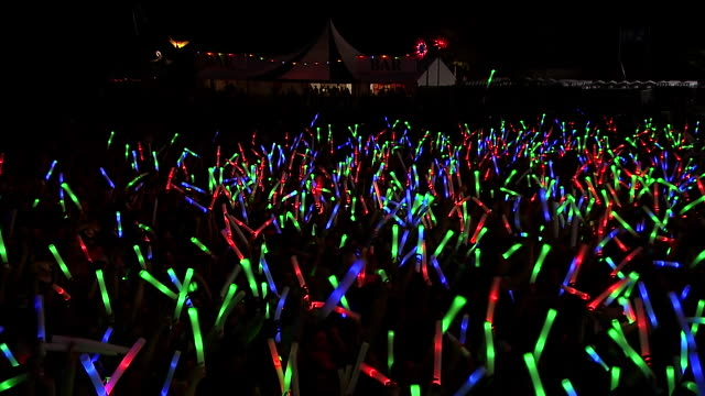 MS CS POV Shot of Festival crowd with giant glow sticks at night / Victoria Park, London, United Kingdom