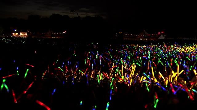 WS CS POV Shot of Festival crowd with giant glow sticks at night / Victoria Park, London, United Kingdom