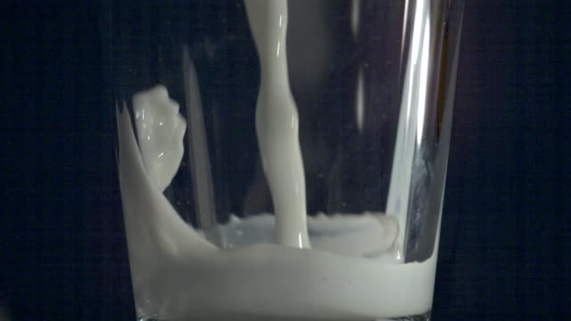 Shot of filling Glass Cup with Milk