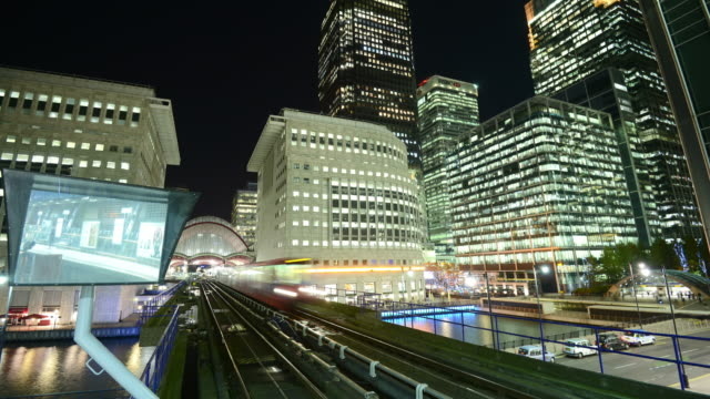 ms la zi t/l shot of financial district canary wharf london and tracks of docklands light railway trains passing rapidly through frame platform is reflecting in large mirror / london, greater london, united kingdom - heranzoomen stock-videos und b-roll-filmmaterial