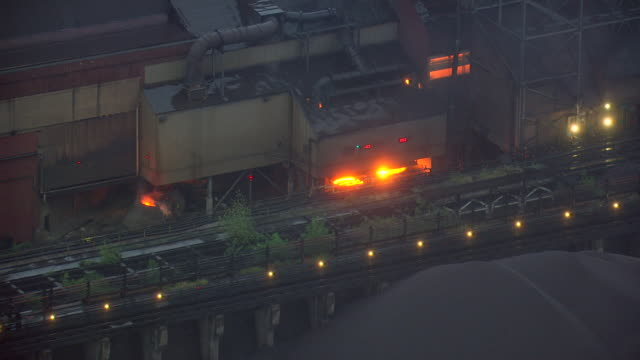 cu aerial shot of fire sparks under buildings at severstal steel plant / dearborn, michigan, united states - dearborn michigan stock videos and b-roll footage
