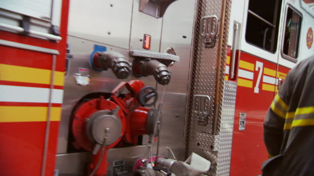 CU Shot of fire truck pulling out of fire station and firemen boarding fire truck and truck driving away / New York, United States