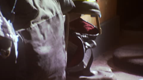 cu tu shot of firemen boots uniforms sitting on bench with harsh lighting in nyfd engine company 7 ladder 1 fire house / new york, united states - terrorism stock videos & royalty-free footage