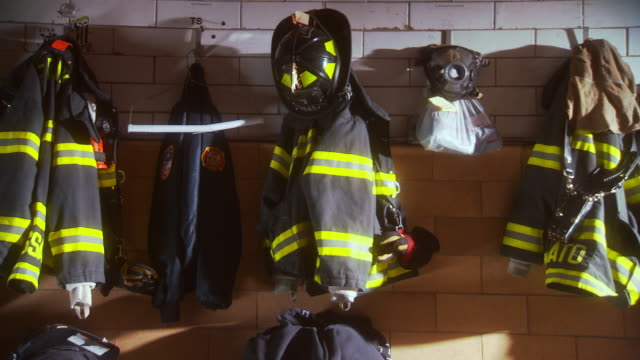 MS ZI Shot of firemen jackets and uniforms hanging on wall in NYFD Engine Company 7 Ladder 1 fire house / New York, United States