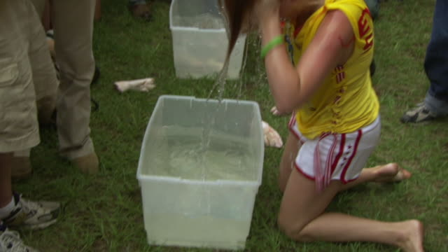 MS TS Shot of first women to finish taking out pigs feet resting from bottom of box filling with water using his mouth only during Summer Redneck Games / Dublin, Georgia, United States