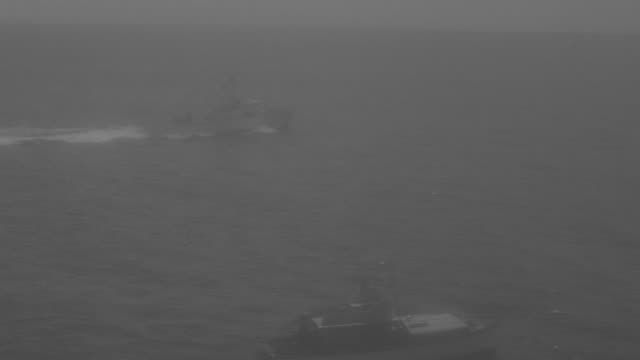 ws ts pan shot of fishing boat sitting in ocean as another boat travelling through waters in background - barca a motore video stock e b–roll