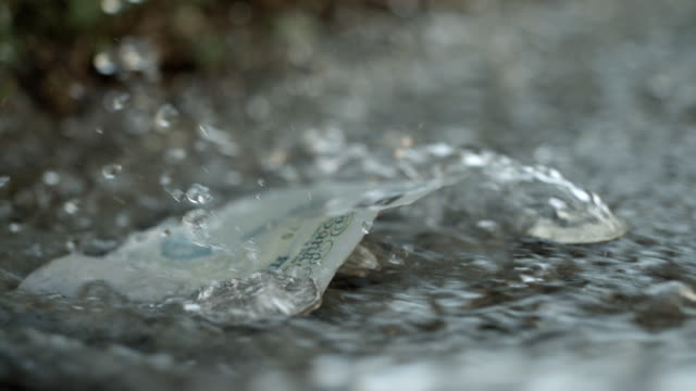 CU SLO MO Shot of five pound note and some coins being washed down drain