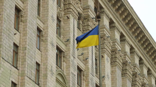 ms shot of flag against building / kiev, ukraine - ukraine stock-videos und b-roll-filmmaterial