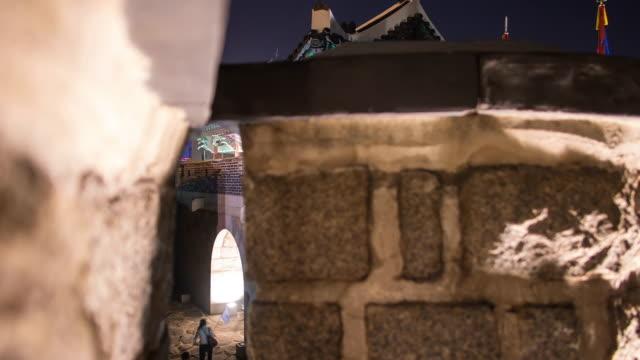 cu t/l tu shot of flag waving in strong wind at changnyongmun gate in suwon hwaseong castle at night (unesco) / suwon, gyeonggi-do, south korea  - besichtigung stock-videos und b-roll-filmmaterial