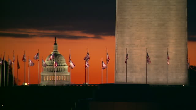 vídeos de stock, filmes e b-roll de ws shot of flags at base of washington monument flapping in wind with us capitol building during sunset / washington, district of columbia, united states - domo
