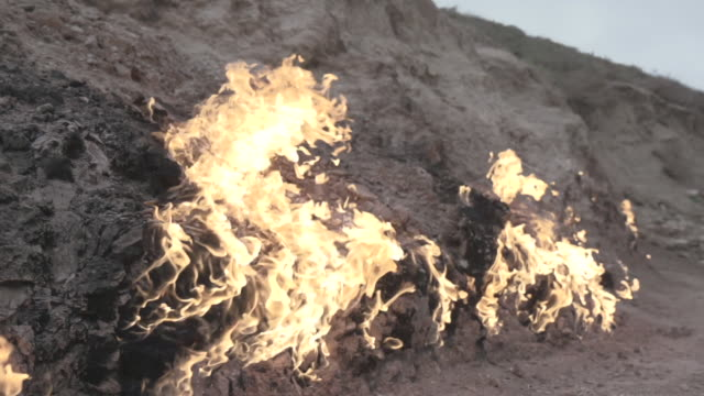 shot of flames erupting from fissures in the ground at an oil field near baku. - baku video stock e b–roll