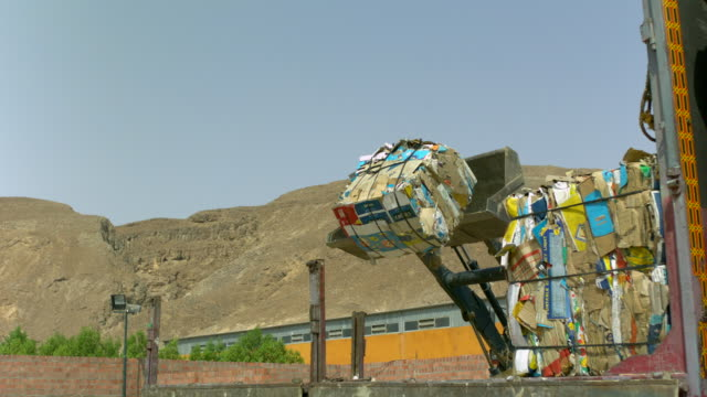 WS SLO MO Shot of flatbed truck with recycle card board blocks Dropping from front loader truck / ElGouna, RED Sea, Egypt