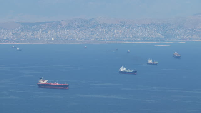 ws aerial shot of flight across piraeus with many freighters and sailboats / piraeus, peloponnese, greece - greece stock videos & royalty-free footage