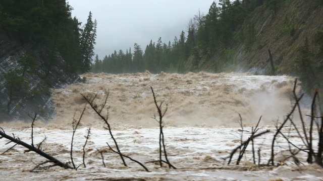 ws shot of flood water cascading down swollen mountain river / banff, canada - banff stock videos & royalty-free footage