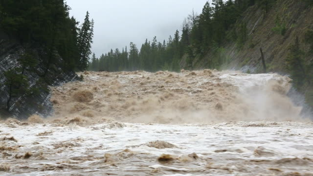 ws shot of flood water cascading down swollen mountain river / banff, canada - flood stock videos & royalty-free footage