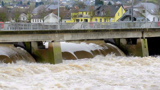 MS Shot of flood waters of brook of under bridge / Schoden, Rhineland Palatinate, Germany