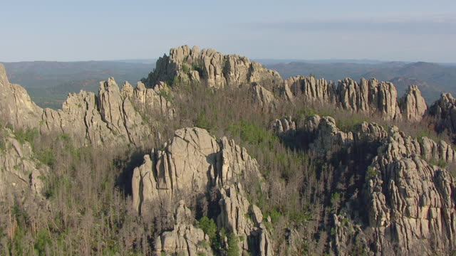 MS AERIAL Shot of fly over rock formations to reveal valley and Black Hills National Forest in Pennington County / South Dakota, United States