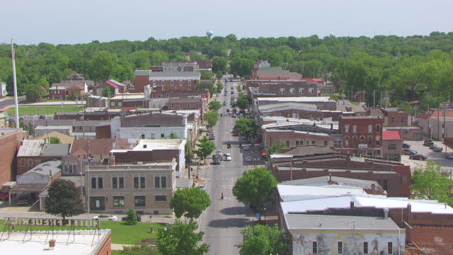 ws aerial td shot of flying over main street traffic and stores / boonville, missouri, united states - ミズーリ州点の映像素材/bロール