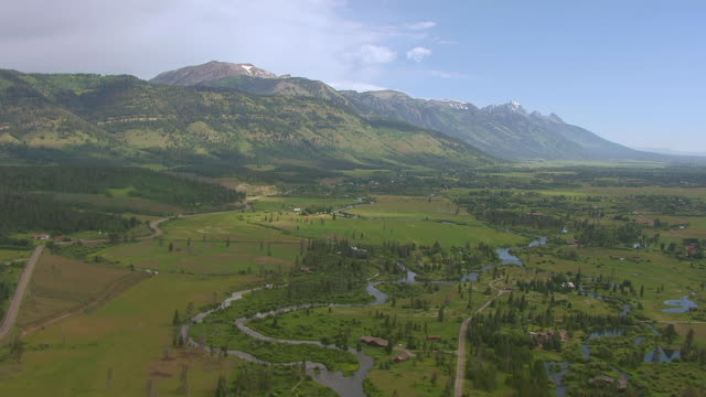 stockvideo's en b-roll-footage met ws aerial shot of flying through valley over snake river with teton mountains on left and gros ventre mountains / wyoming, united states - snake river