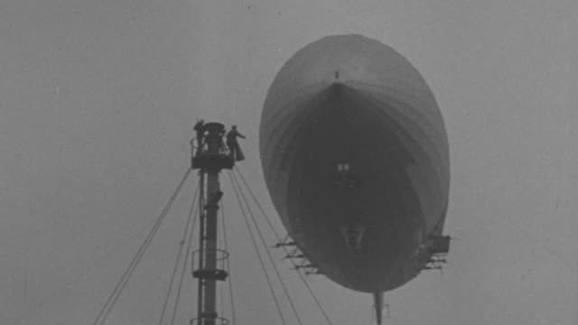 MS Shot of flying Zeppelin and men on tower guiding Zeppelin for landing