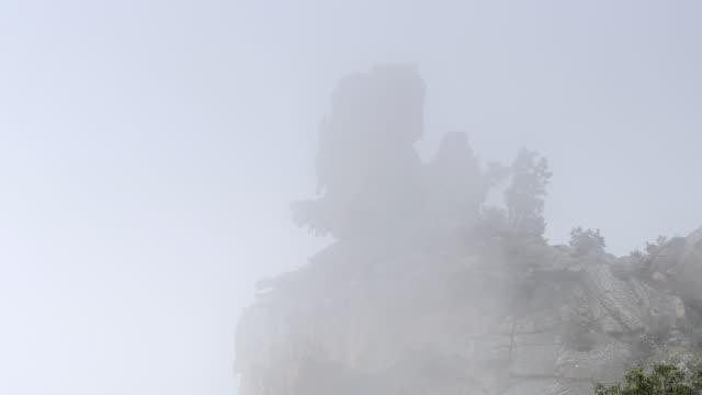 ms shot of fog moves over fantastic rocks of calanche of piana, unesco world heritage site / porto, corsica, france - ピアナ点の映像素材/bロール