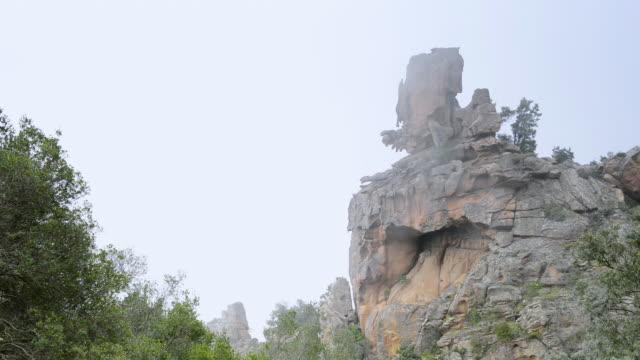 ms shot of fog moves over fantastic rocks of calanche of piana, unesco world heritage site / porto, corsica, france - カランシェ点の映像素材/bロール