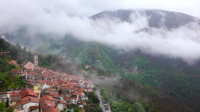WS Shot of fog moving over mountain village and valley / Basati, Tuscany, Italy