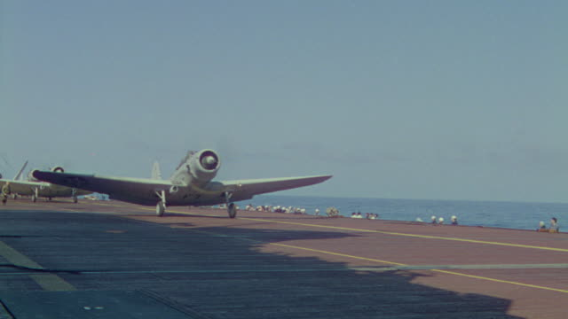 ms pan shot of following bombers taking off from carrier - flugzeugträger stock-videos und b-roll-filmmaterial