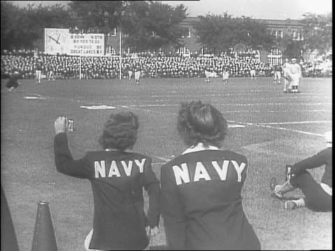 vidéos et rushes de shot of football field with marching band / crowd of men in navy uniform in football stadium stands / cheerleaders cheering with football field... - pom pom girl