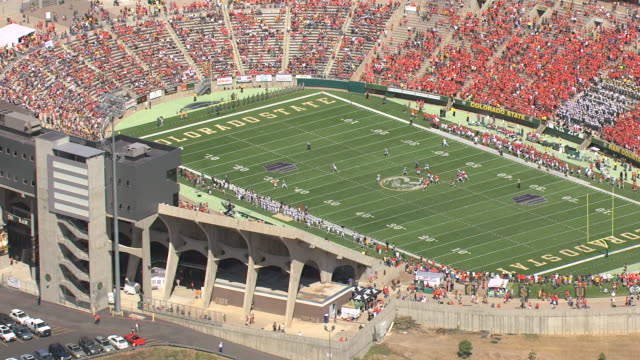 ms ds zi aerial shot of football players on field and spectators on seats during football game at colorado state university football stadium / fort collins, colorado, united states - アメリカンフットボール場点の映像素材/bロール