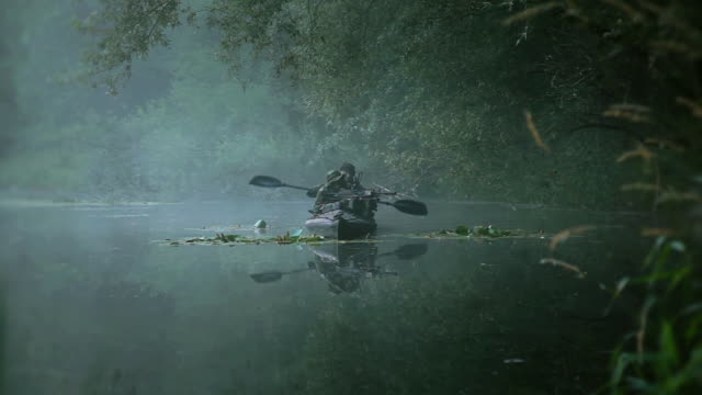 vídeos de stock, filmes e b-roll de ms shot of force recon soldiers in camouflaged folding boat moving in river during reconnaissance mission in jungle with light machine gun in his arms / swamp, virginia, united states - armamento